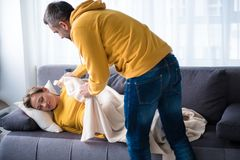 Careful man putting quilt on expectant lady napping on sofa Royalty Free Stock Photos