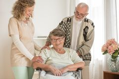 Husband taking care of his wife while the nurse is smiling stock images