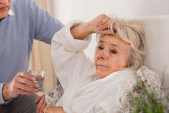 Husband taking care of wife. Husband taking care of his elderly sick wife Stock Photos