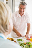 Husband Talking To Wife While Preparing meal Stock Photography