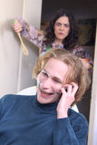Husband telephoning, wife angry Royalty Free Stock Image