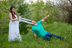 Husband tries to escape from a pregnant wife Stock Photos