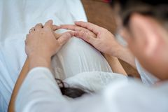 Husband uses hand to touch belly of pregnant wife in white dress, with soft sunlight In morning relaxed atmosphere,concept royalty free stock photos