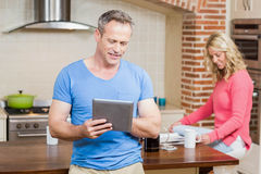 Husband using tablet while wife having breakfast Royalty Free Stock Photography