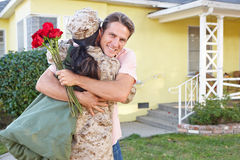 Husband Welcoming Wife Home On Army Leave. Hugging Stock Images