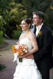 Husband and wife. Wedding bride and her new husband. She is holding her beautiful bridal bouquet of flowers. They are looking away from the camera stock photo