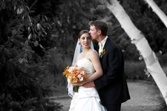 Husband and wife. Wedding bride and her new husband. She is holding her beautiful bridal bouquet of flowers. This is done in mixed black and white and color Royalty Free Stock Image