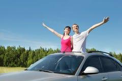 Husband, wife arrange hands in hatch of car. In field Stock Image