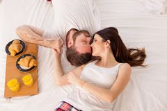 Husband and wife in bed in the morning woke up to breakfast in bed royalty free stock image