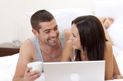 Husband and wife in bed using a laptop Royalty Free Stock Image