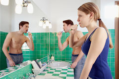 Husband and wife brushing teeth in bathroom Stock Photos