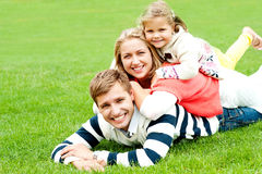 Husband, wife and child piled on each other. Having fun outdoors Royalty Free Stock Photography