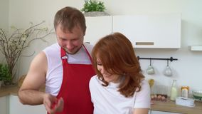 The husband with the wife cook a tasty breakfast in kitchen. All family assembled in kitchen. A happy close-knit family. On this video you can see as the husband stock video footage