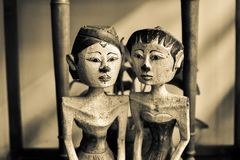 Old vintage traditional wooden statues of husband and wife with local custom fashion. Husband and wife couple wooden statues sitting together in a traditional stock images