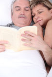 Husband and wife cuddling in bed Royalty Free Stock Photos