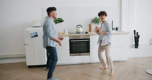 Husband and wife dancing in kitchen having fun enjoying leisure time at home. Husband and wife happy young people are dancing in kitchen having fun enjoying stock video