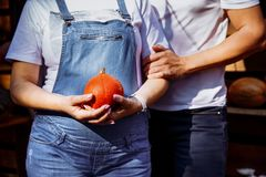 Husband and pregnant wife in denim suits hug each other, she holds a pumpkin in her hands. stock photography