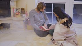 Husband and wife didn`t notice that the smoke from fireplace pours into the room. Married couple sits on floor near fireplace and relaxing with book. Husband stock video footage