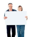 Husband and wife displaying advertising board Stock Images