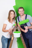 Husband and wife doing DIY renovations. And redecorating their new home together painting it a bright green Royalty Free Stock Photos