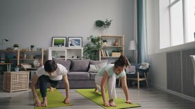 Husband and wife doing yoga together at home enjoying relaxing practice. Husband and wife cute couple are doing yoga together at home enjoying relaxing practice stock video