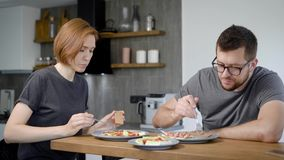 Husband and wife eat breakfast together. Behind the wooden bar, behind the modern kitchen interior. stock video