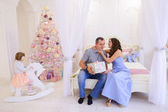 Husband and wife give each other Christmas gifts in bright spaci. Young happy family, mother, father and daughter, girl in Christmas mood. Woman pulls out from Royalty Free Stock Photos