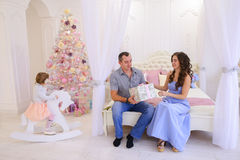 Husband and wife give each other Christmas gifts in bright spaci. Young happy family, mother, father and daughter, girl in Christmas mood. Woman pulls out from Royalty Free Stock Images