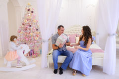 Husband and wife give each other Christmas gifts in bright spaci. Young happy family, mother, father and daughter, girl in Christmas mood. Woman pulls out from Stock Image