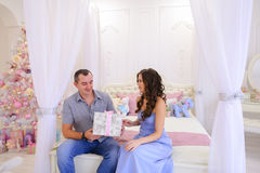 Husband and wife give each other Christmas gifts in bright spaci. Young happy family, mother, father and daughter, girl in Christmas mood. Woman pulls out from Stock Photo
