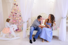 Husband and wife give each other Christmas gifts in bright spaci. Young happy family, mother, father and daughter, girl in Christmas mood. Woman pulls out from Royalty Free Stock Photography