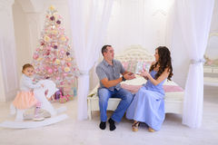 Husband and wife give each other Christmas gifts in bright spaci. Young happy family, mother, father and daughter, girl in Christmas mood. Woman pulls out from Stock Photos