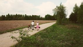 Husband and wife go with a bicycle and baskets go on the road against the background of the field. stock footage