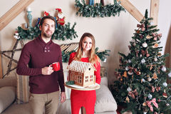 Husband and wife hold gingerbread house  embrace near christmas tree Stock Photography