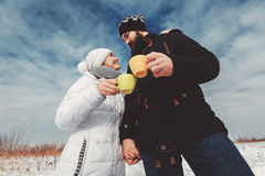 Husband and wife hold hands and drink hot coffee in snowy field royalty free stock images