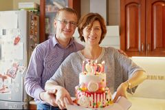 Husband and wife are holding a cake with candles royalty free stock image