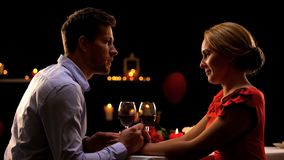 Husband and wife holding hands and admiring each other on romantic dinner stock images
