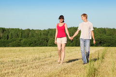Husband, wife holding hands walk in field Stock Images