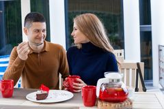 Husband with wife on holiday drink hot coffee and tea royalty free stock photography