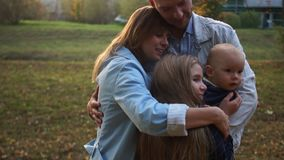 Husband and wife hug their two children in the autumn park. Happy family on a walk. Sunset in the city park stock footage
