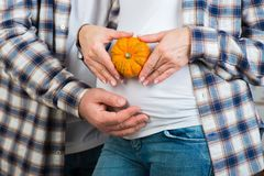Husband and wife in jeans and a plaid shirt holds little pumpkin in their hands. Couple posing a heart with their fingers on belly. Of expectant mother royalty free stock images