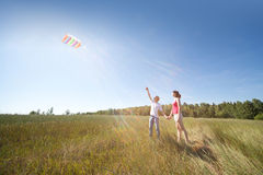 Husband, wife launch kite in field Stock Photo