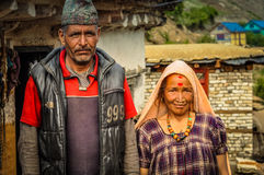Husband and wife in Nepal. Dolpo, Nepal - circa June 2012: Native man with cap wears grey vest and red shirt with his wife in purple dress with headcloth in Stock Image