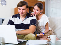 Husband and wife ordering products. Husband ordering products and services online according notes of wife Royalty Free Stock Photography