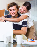 Husband and wife ordering products. Husband ordering products and services online according notes of caucasian wife Stock Photography
