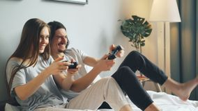 Husband and wife in pajamas playing video game in bed at home, man winning. Husband and wife in pajamas are playing video game in bed at home, handsome bearded stock video footage