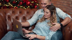Young couple shopping online at home on Christmas Eve stock video footage