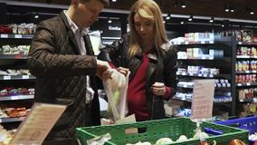Happy couple is picking cucumbers in a supermarket