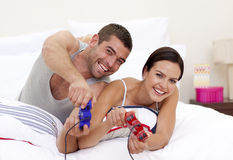 Husband and wife playing videogames in bed Royalty Free Stock Photo