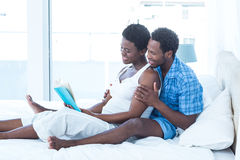 Husband and wife reading book on bed Royalty Free Stock Photos